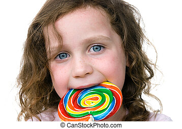 Little girl smiling with her candy pin wheel sucker