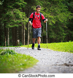 active handsome young man nordic walking/hiking in...