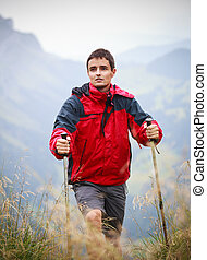active handsome young man nordic walkinghiking in mountains,...