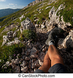 Hiker resting for a while during a tough hike in Alps