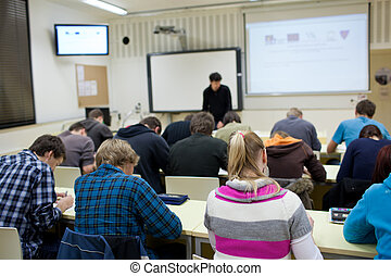 pretty female college student sitting in a classroom full of...