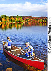 canoeing in fall - People canoeing on scenic lake in fall,...