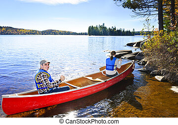 Canoeing near lake shore - Family in red canoe near rocky...
