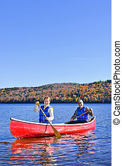 Canoe trip on scenic lake in fall - Family canoeing on Lake...