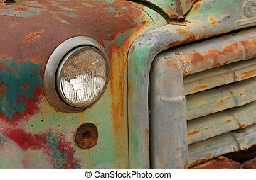 A green and red painted rusty front grill of an antique...