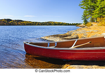 Red canoe on shore - Red canoe on rocky shore of Lake of Two...