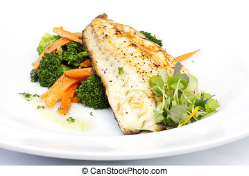 Fresh black cod on bed of broccoli and carrots with a touch...