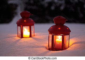 Two burning lanterns in the snow