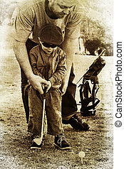 father and son play golf - father teaches his toddler son...