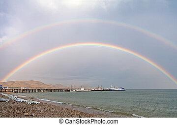 Double rainbow on sea beach