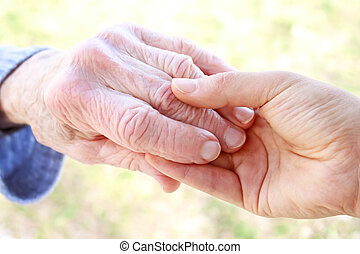 Senior and young holding hands - Senior and Young Women...