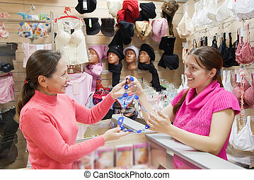 Saleswoman and customer with  necklace