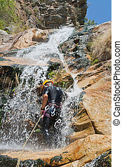 Men descending waterfall - Men descending in rappeling a...