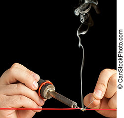 Technician Soldering a Red Wire. - Soldering Tech soldering...