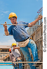 Construction workers installing formwork frames - Authentic...