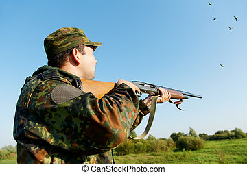 hunter shooting with rifle gun - Male hunter in camouflage...