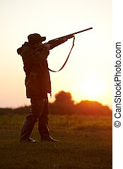 hunter aiming with rifle gun - Male hunter in camouflage...