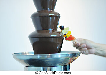 liquid chocolate fountain and fresh fruits on stick - liquid...
