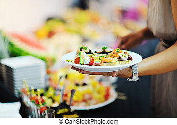 womanl chooses tasty meal in buffet at hotel banquet party...