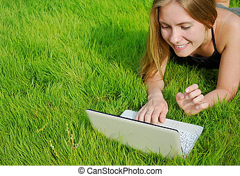 girl with netbook in park - girl with netbook on lawn in...