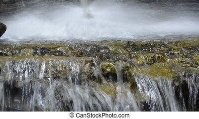 Splashing water on a stone in a small river with water fall