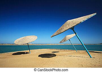 Wicker Beach Umbrella with wicker wind breaks.
