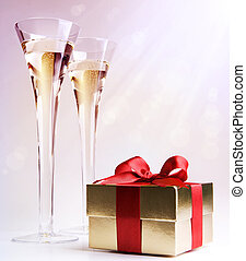 two glasses of champagne and a gift