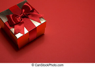 art golden gift box with a red bow on red background