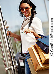 Happy shopper - Image of happy female with paperbags opening...