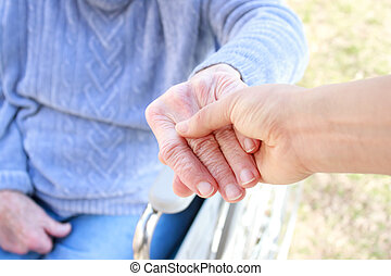 Helping Hand - Young holding senior lady's hand in...