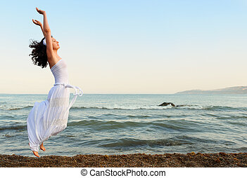 The young woman jumps on seacoast. A picturesque landscape