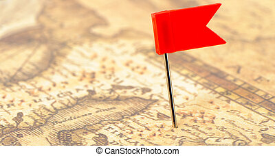 Flag red a pin on old map. Photo closeup. Selective focus