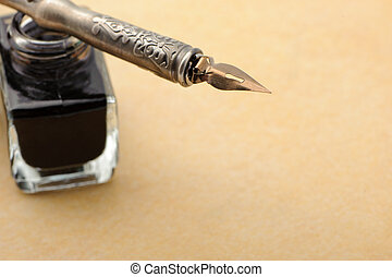 Feather quill and inkwell on an old paper. Photo closeup