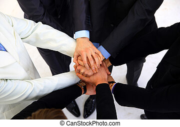 group of business people making a pile of hands in a light and modern office environment