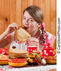 Girl in traditional clothes eating pancake during Maslenitsa...
