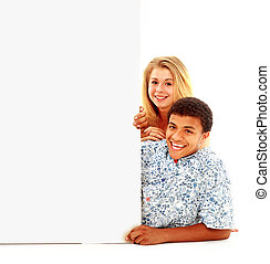 Portrait of happy men and women standing with a billboard against white background