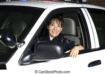 patrol car - a female police officer sitting in her patrol...