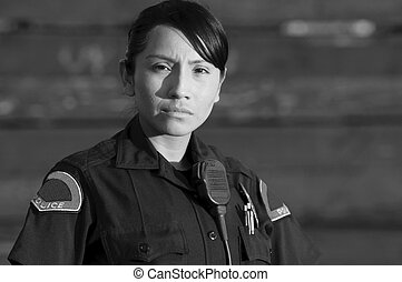 police officer - a Hispanic police officer standing with a...