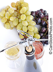 Bottle of wine with aperitive, glasses of wine and grapes isolated in white