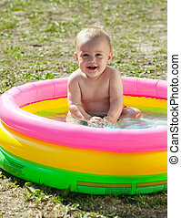 Happy baby swimming in inflatable pool - Happy baby swimming...