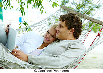Couple with laptop - Happy dates with laptop lying in...