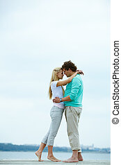 Honeymoon - Image of affectionate man and woman embracing...