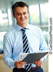 Happy boss - Portrait of attractive male with papers looking...