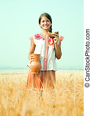 Girl with bread at rye field - Girl with bread and jug of...