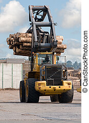 Skidder hauling logs at sawmill