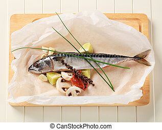 Fresh mackerel and other ingredients on cutting board