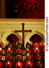 Cross and Candles - Rows of red lit candles and a cross at a...
