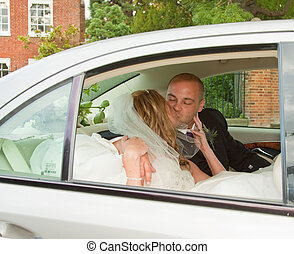 Wedded Bliss - A pair of newlyweds sharing a kiss in the...