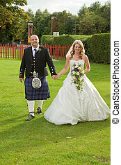 Smiling Newlyweds - A young newlywed couple walking hand in...