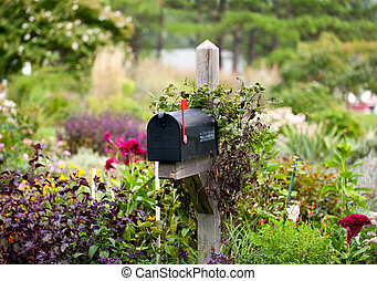 US mailbox with flag raised in flowers - Traditional mail...
